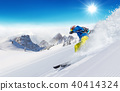 Skier on piste running downhill 40414324
