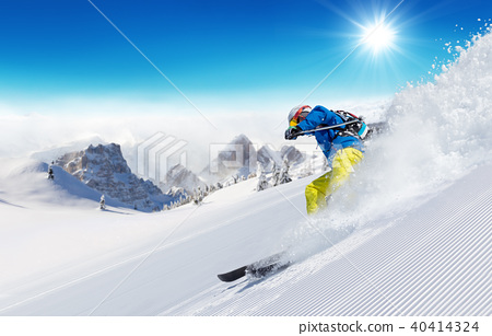 Skier on piste running downhill 40414324