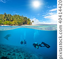 Underwater coral reef with scuba divers and manta 40414420