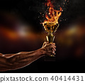 Muscular man arm holding burning trophy cup on black background 40414431