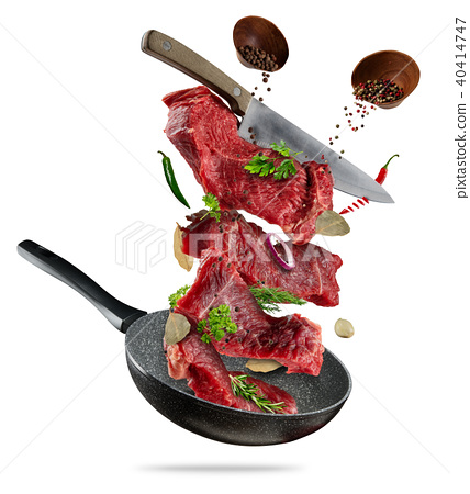 Flying raw steaks with cooking ingredients from pan 40414747