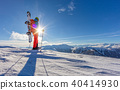 Snowboarder walking on snowshoes in powder snow. 40414930