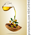Olive oil with flying olives in wooden bowl 40414940