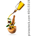 Olive oil with flying olives in wooden mortar 40415019