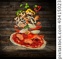 Flying ingredients with pizza dough, on wooden background 40415023