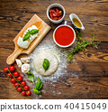 Pizza dough with tomato sauce on wooden table 40415049