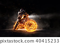 Dark motorbiker staying on burning motorcycle, separated on black background. 40415233