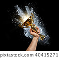 Man holding up a gold trophy cup 40415271