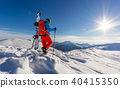 Snowboarder walking on snowshoes in powder snow. 40415350