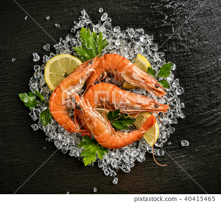 Cooked prawns served on black stone 40415465