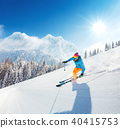 Skier on piste running downhill 40415753