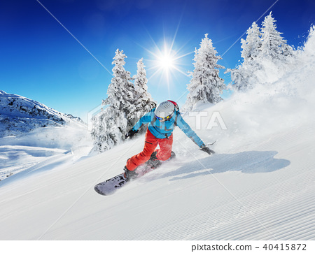 Young man snowboarder running down the slope in Alpine mountains 40415872