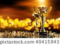 Champion golden trophy on wood table with spot lights on background 40415943