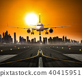 Landing commercial airplane at the runway, modern city on background 40415951