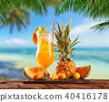 Fresh orange drink placed on wooden planks, blur beach on background 40416178