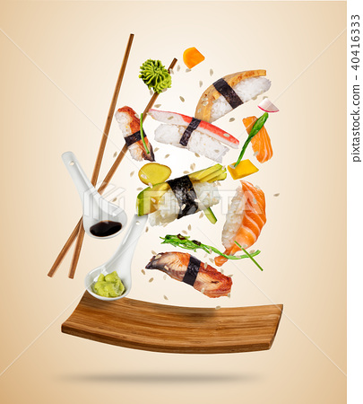 Flying sushi pieces served on wooden plate, separated on colored background 40416333