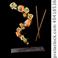 Flying pieces of sushi with wooden chopsticks and stone plate, isolated on black background. 40416536