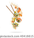 Flying pieces of sushi with wooden chopsticks, separated on white background. 40416615
