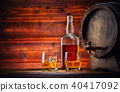 Glasses, bottle and keg of whiskey with ice cubes served on wood 40417092