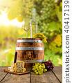 White wine served on wooden barrel, vineyard on background 40417139