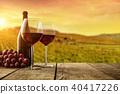 Red wine served on wooden planks, vineyard on background 40417226