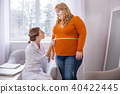 Serious nutritionist talking with a plump woman 40422445