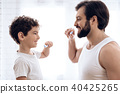 Happy father and son brush teeth 40425265