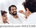 Happy father and son brush teeth  40425286