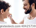 Happy father brushes teeth of young son  40425739