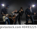 Musician band hand holding the microphone and singing a song and playing music instrument with Fellow band musicians on black background with spot light and lens flare, musical concept 40493225