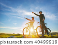 Biker couple with mountain bike pointing in distance at countryside 40499919