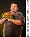 Fat man eating fast food hamberger. Breakfast for overweight person. 40500259
