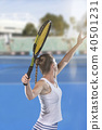 Rear view of tennis player serving during a match 40501231