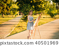 Beautiful girl standing in the park and draws a picture using a palette with paints and a spatula. 40501969