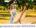 Beautiful girl standing in the park and draws a picture using a palette with paints and a spatula. 40502005