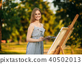 Beautiful girl standing in the park and draws a picture using a palette with paints and a spatula. 40502013