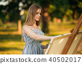 Beautiful girl standing in the park and draws a picture using a palette with paints and a spatula. 40502017