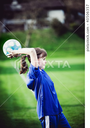 Teen girl playing soccer at local stadium outside 40506357