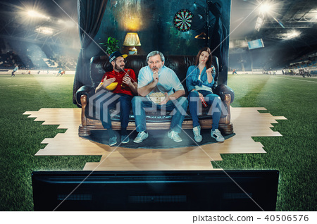 Ardent fans are sitting on the sofa and watching TV in the middle of a football field. 40506576