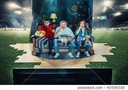 Ardent fans are sitting on the sofa and watching TV in the middle of a football field. 40506580