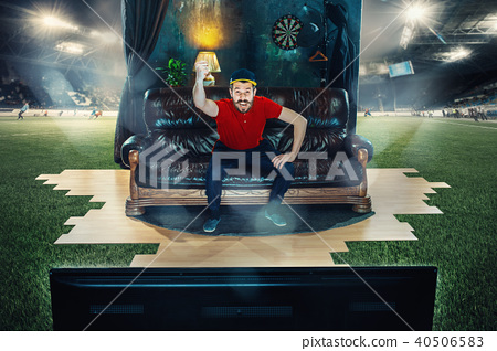 Male fan sitting on the sofa and watching TV in the middle of a football field. 40506583