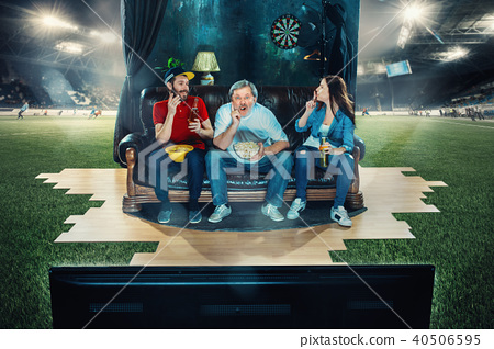 Ardent fans are sitting on the sofa and watching TV in the middle of a football field. 40506595
