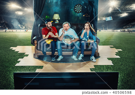 Ardent fans are sitting on the sofa and watching TV in the middle of a football field. 40506598