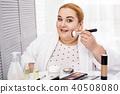 Joyful plump woman applying make-up 40508080