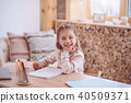 Joyful positive girl drawing a picture 40509371
