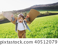 Happy toddler boy with wings playing outside in spring nature. 40512079