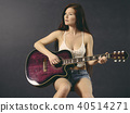 Woman with freckles and red hair playing acoustic guitar 40514271
