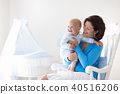Mother and baby at home. Mom and child in bedroom. 40516206