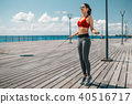 Happy slim girl using jumping-rope on seafront 40516717