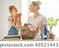 mother and daughter ironing at home 40521443